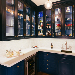 Design ideas for a medium sized classic l-shaped wet bar in Los Angeles with a submerged sink, glass-front cabinets, blue cabinets, marble worktops, white splashback, porcelain splashback and dark hardwood flooring.