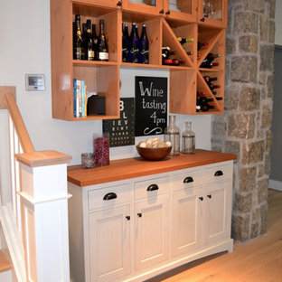 Design ideas for a small traditional single-wall wet bar in Boston with shaker cabinets, white cabinets, light hardwood flooring and beige floors.