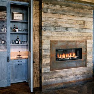 Foto de bar en casa con fregadero lineal, de estilo de casa de campo, con fregadero bajoencimera, puertas de armario azules, suelo de madera oscura y armarios con paneles empotrados