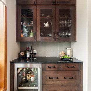 Ispirazione per un piccolo angolo bar tradizionale con ante di vetro, ante in legno bruno, nessun lavello, top in quarzo composito, paraspruzzi beige, paraspruzzi in gres porcellanato, moquette, pavimento beige e top nero