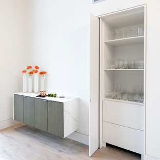 Inspiration for an expansive contemporary single-wall bar cart in Dallas with recessed-panel cabinets, white cabinets, marble worktops and light hardwood flooring.