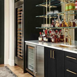 Immagine di un armadio bar tradizionale con lavello sottopiano, ante in stile shaker, ante nere, paraspruzzi a specchio, parquet chiaro e top bianco
