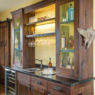 Example of a mountain style single-wall medium tone wood floor wet bar design in Other with a drop-in sink and dark wood cabinets