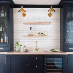 ニューヨークの小さいトラディショナルスタイルのおしゃれなウェット バー (I型、ドロップインシンク、シェーカースタイル扉のキャビネット、青いキャビネット、木材カウンター、白いキッチンパネル、サブウェイタイルのキッチンパネル) の写真