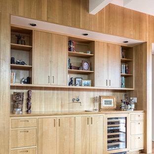 Imagen de bar en casa con fregadero lineal, contemporáneo, con fregadero bajoencimera, armarios con paneles lisos, puertas de armario de madera clara, encimera de madera, salpicadero marrón, salpicadero de madera y suelo de madera en tonos medios