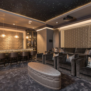 This is an example of an expansive classic enclosed home cinema in Belfast with grey walls, carpet, a projector screen and grey floors.
