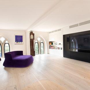 Nordisches Heimkino mit weißer Wandfarbe, hellem Holzboden und Wand-TV in London