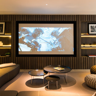 Mid-sized contemporary home theatre in London with brown walls and beige floor.