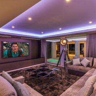 Foto de cine en casa cerrado, actual, grande, con paredes grises, moqueta, televisor colgado en la pared y suelo marrón