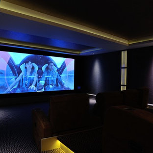 Inspiration for a large contemporary open plan home cinema in London with carpet and a built-in media unit.
