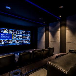 Ejemplo de cine en casa cerrado, minimalista, de tamaño medio, con paredes marrones, moqueta y televisor colgado en la pared