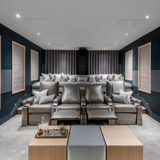 Photo of a contemporary home cinema in Other with blue walls, carpet, a projector screen and grey floors.