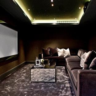 Abgetrenntes Modernes Heimkino mit brauner Wandfarbe, Teppichboden, Leinwand und grauem Boden in London
