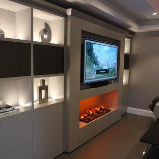 Mittelgroßes, Offenes Modernes Heimkino mit beiger Wandfarbe, Laminat, Multimediawand und braunem Boden in Sussex