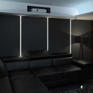Photo of a large modern open concept home theatre in London with grey walls, slate floors and a projector screen.