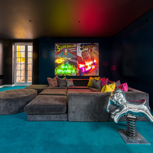 This is an example of an expansive bohemian enclosed home cinema in London with blue walls, carpet and blue floors.