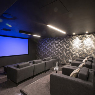 Medium sized contemporary enclosed home cinema in London with grey walls, a projector screen, grey floors and carpet.