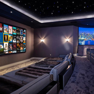 Photo of a large contemporary enclosed home cinema in Berkshire with brown walls, carpet, grey floors and a projector screen.