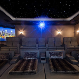 Large contemporary enclosed home cinema in Berkshire with brown walls, carpet and a projector screen.