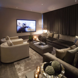 This is an example of a large contemporary open concept home theatre in West Midlands with grey walls, ceramic floors and a projector screen.