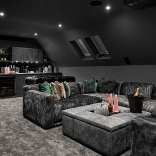 This is an example of a large contemporary home cinema in Buckinghamshire with black walls, carpet and grey floors.