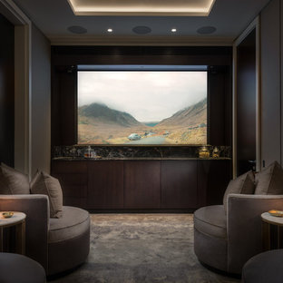 Medium sized contemporary enclosed home cinema in London with grey walls, carpet, a projector screen and grey floors.