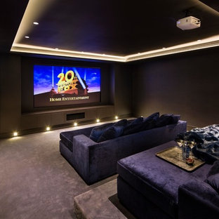 Medium sized contemporary enclosed home cinema in London with brown walls, carpet, a projector screen and purple floors.