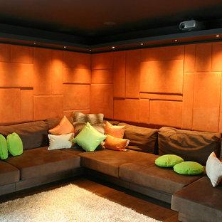 Imagen de cine en casa cerrado, minimalista, de tamaño medio, con parades naranjas, suelo de madera oscura y pantalla de proyección