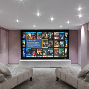 This is an example of a small contemporary enclosed home theatre in London with pink walls, carpet and a projector screen.