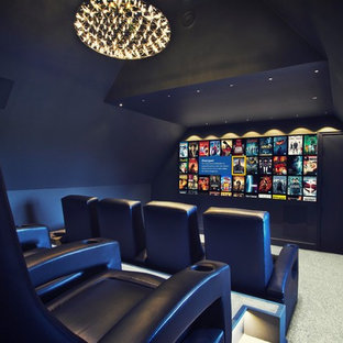 This is an example of a contemporary enclosed home cinema in Kent with blue walls, carpet and a projector screen.