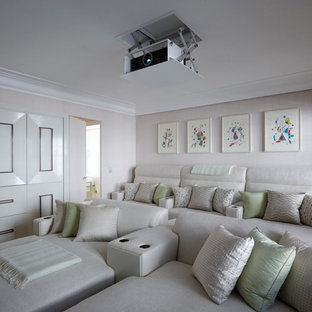 Mid-sized transitional enclosed home theater photo in London with beige walls and a projector screen
