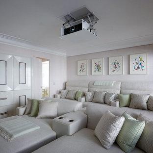 Idée de décoration pour une salle de cinéma tradition fermée et de taille moyenne avec un mur beige et un écran de projection.