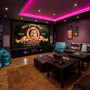 Medium sized traditional enclosed home cinema in Other with purple walls, medium hardwood flooring, a projector screen and brown floors.