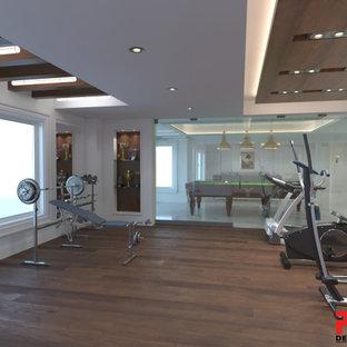 Foto di una grande sala pesi vittoriana con pavimento in legno massello medio, pavimento marrone e pareti bianche