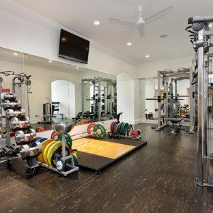Modelo de sala de pesas clásica, grande, con paredes blancas, suelo vinílico y suelo marrón