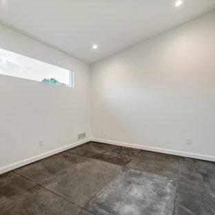 Foto di una palestra multiuso minimalista con pareti bianche, pavimento in vinile e pavimento nero