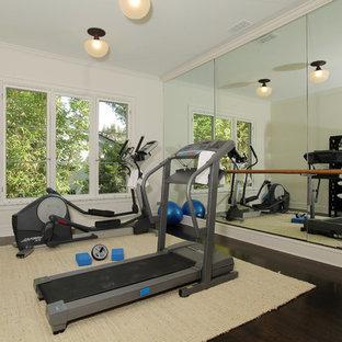Foto de gimnasio tradicional con paredes blancas y suelo de madera oscura