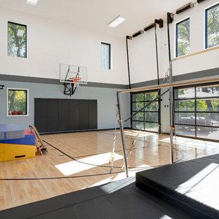 Idee per un grande campo sportivo coperto design con pareti multicolore, parquet chiaro e pavimento marrone