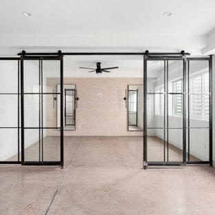 Esempio di una palestra multiuso minimalista con pareti bianche, pavimento in cemento e pavimento grigio
