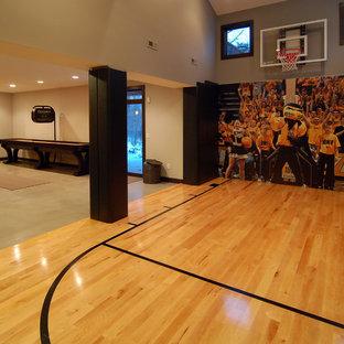 Diseño de pista deportiva cubierta contemporánea con paredes beige y suelo de madera clara