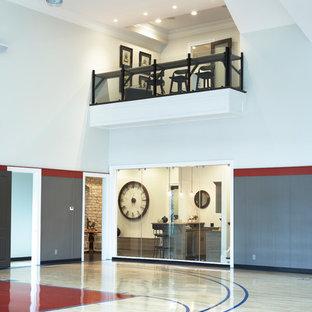 Geräumiger Moderner Fitnessraum mit Indoor-Sportplatz, weißer Wandfarbe und hellem Holzboden in Sonstige