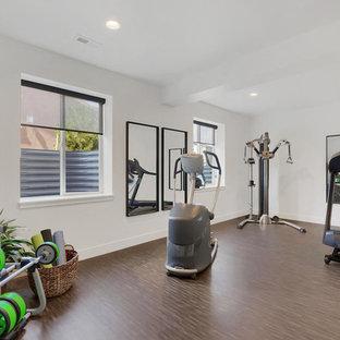 デンバーのミッドセンチュリースタイルのおしゃれなトレーニングルーム (白い壁、ラミネートの床、茶色い床) の写真