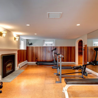 This is an example of a large classic home weight room in Boston with white walls and cork flooring.