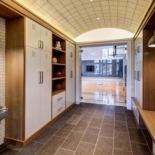 オレンジカウンティの巨大なトランジショナルスタイルのおしゃれな室内コート (白い壁、磁器タイルの床、茶色い床) の写真