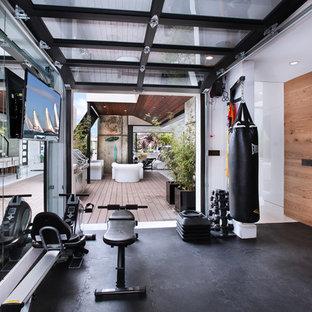 Multifunktionaler Moderner Fitnessraum mit weißer Wandfarbe und schwarzem Boden in Orange County