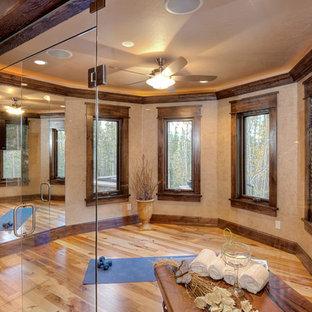 Klassisk inredning av ett hemmagym med yogastudio, med beige väggar, ljust trägolv och brunt golv