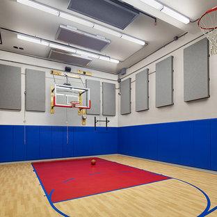 Immagine di un campo sportivo coperto tradizionale con pareti blu e pavimento in legno verniciato