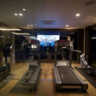 Moderner Fitnessraum mit braunem Holzboden in Cheshire