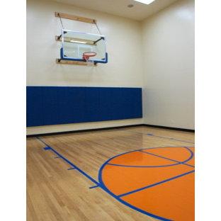 Großer Moderner Fitnessraum mit Indoor-Sportplatz, weißer Wandfarbe und gebeiztem Holzboden in Miami