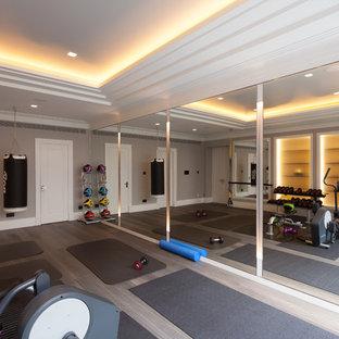 Multifunktionaler Klassischer Fitnessraum mit beiger Wandfarbe, hellem Holzboden und grauem Boden in London